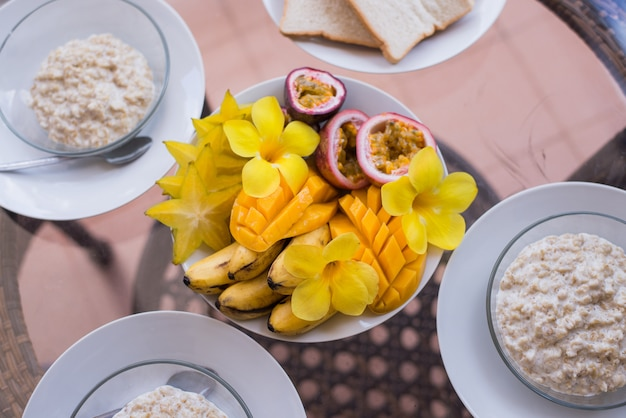 Oatmeals porridge and fruit bowl with mango, banana, passionfruit and flowers.