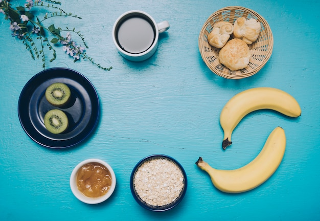 Oats; banana; kiwi; jam; coffee cup and bread on blue textured background