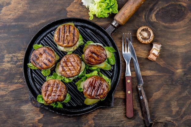 グリルしたポートベローパンマッシュルームハンバーガーの鋳鉄製グリル鍋ob木製、トップビュー