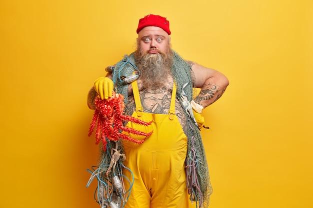 Marinaio maschio barbuto obeso con rete da pesca