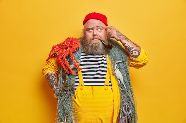 太ったひげを生やした男性の船乗りの漁網