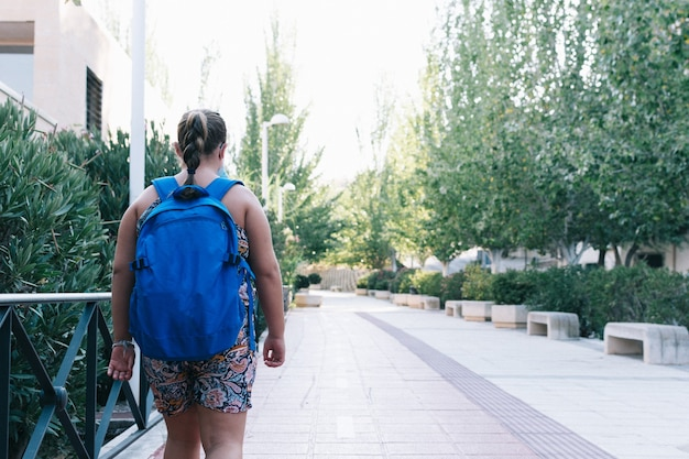 Obese blonde girl with blue backpack on her way to school