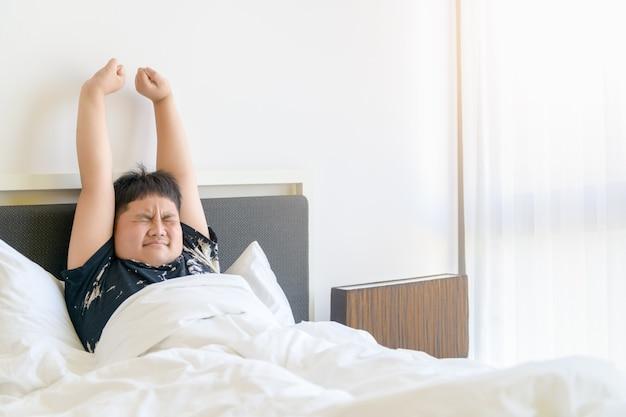 肥満の少年は朝起きてベッドで腕を伸ばします。怠惰で休む