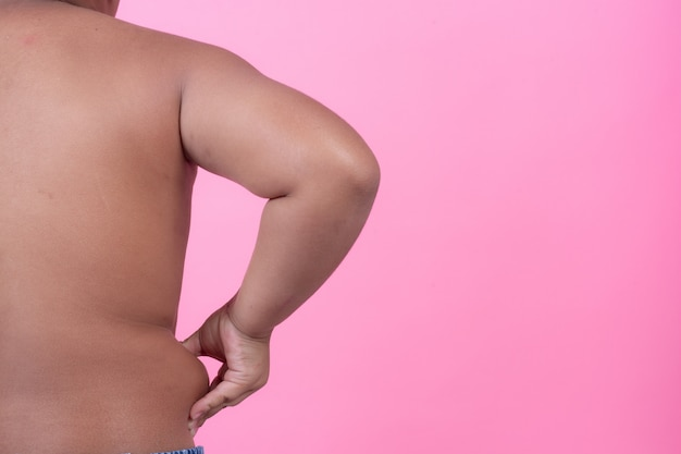 Obese boy who is overweight on a pink background.