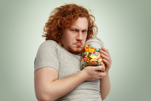 Obese chubby european man with ginger curly hair holding jar of sweets tight