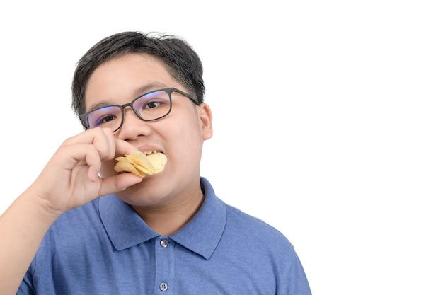 白い背景、不健康な食品またはジャンクフードの概念で隔離のポテトチップスを食べる肥満の太った少年