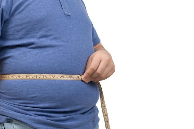 白い背景で隔離の胃のテープを測定する肥満の太った少年、健康と減量の概念
