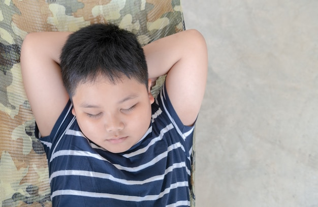 Obese fat boy sleep on cradle in park