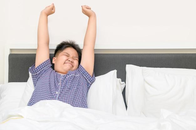 Тучный толстый мальчик просыпается и растягивается на кровати утром,