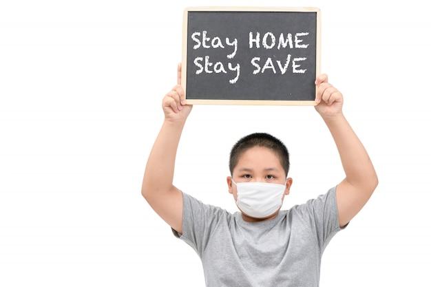 肥満の太った少年の着用マスクが黒板を示し、ホームステイで言葉を保存する