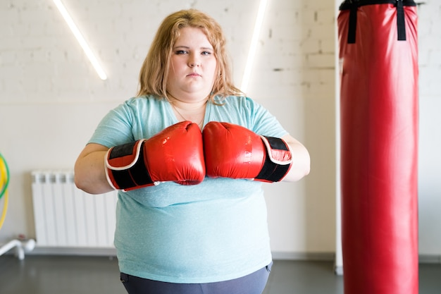 Obese female boxer posing in gym