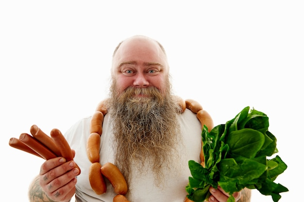 An obese man with sausages around the neck holding spinach and sausages
