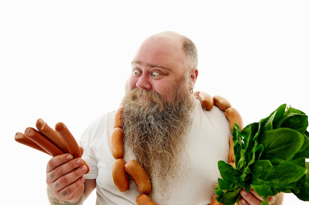 An obese manwith a bunch of sausages around the neck looking at sausages and holding spinach on the other hand try to choose what is more healthy