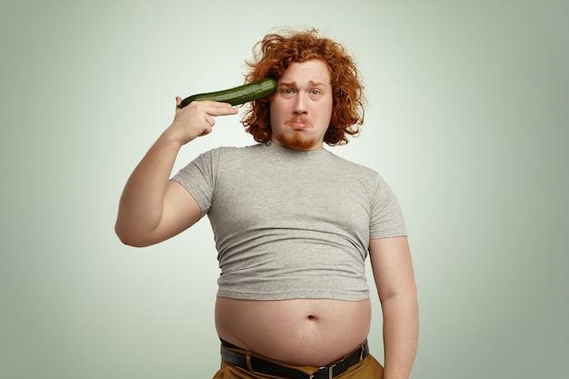 即興のキュウリの銃から自分自身を撃つ準備ができている肥満の太りすぎの若い赤毛の男性