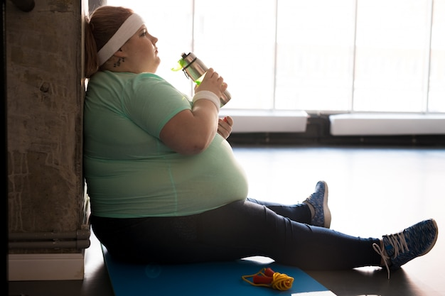 Obese woman drinking water