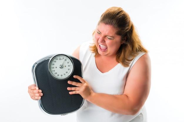 スケールで怒っている肥満の女性 Premium写真