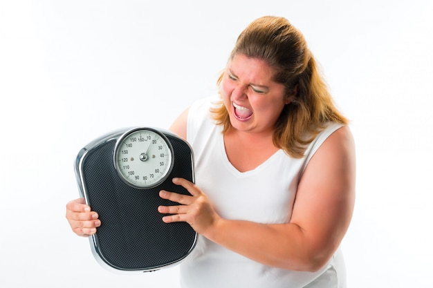 Obese woman looking angry at scale