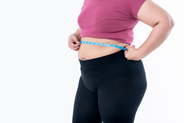 肥満の女性は巻尺を使用して彼女の腹の脂肪を締めます