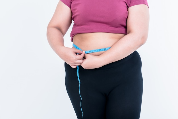 Obese woman use a tape measure fasten her belly fat