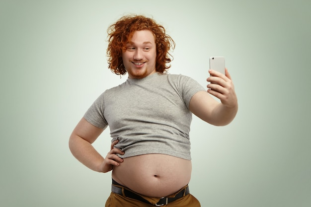 Obese young male with curly ginger hair and beard holding mobile phone, posing for selfie, looking with flirty smile while his fat belly hanging out of grey shrunk t-shirt and jeans pants