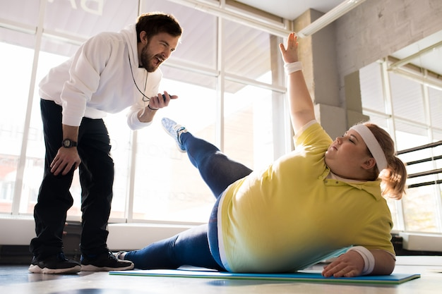 Obese young woman working out with coach