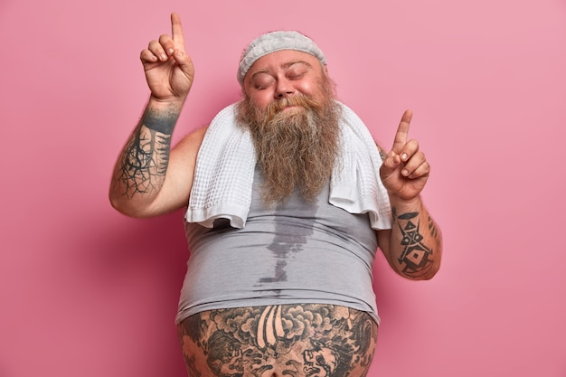 Obesity and sport concept. joyful overweight man dances carefree has sweaty body tattooed arms points upwards isolated on pink wall, does exercises at home, burns calories after eating fast food