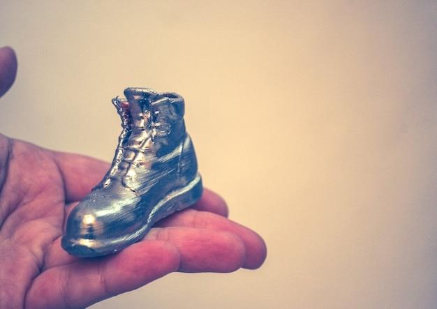 Объект в виде ботинка напечатан на 3д принтере и покрыт эмалью на руке крупным планом. изолированные на белом фоне. прогрессивные современные аддитивные технологии. копировать spase