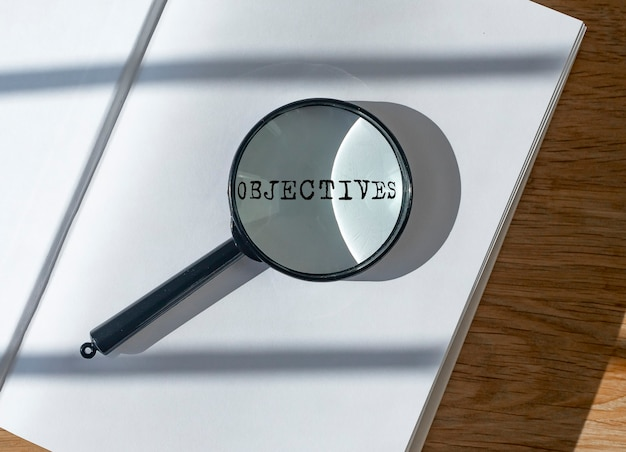 Objective word through magnifying glass loupe concept of goals and motivation