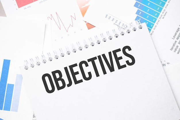 Objectives text on paper on the chart surface with pen