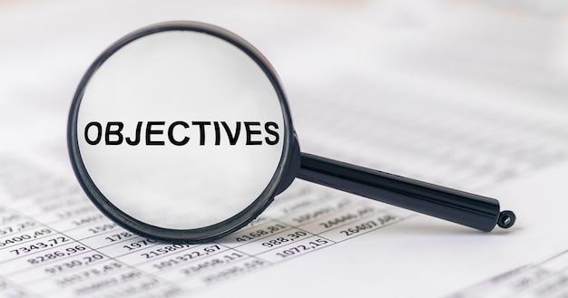 Цели слово надпись через увеличительное стекло на финансовых документах, бизнес-целях.