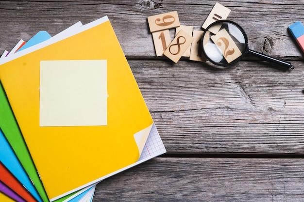 Объекты для образования, школьные принадлежности, офис на деревянном фоне