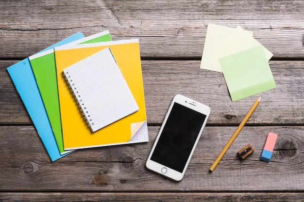 Объекты для образования, школьные принадлежности, офис со смартфоном на деревянном фоне