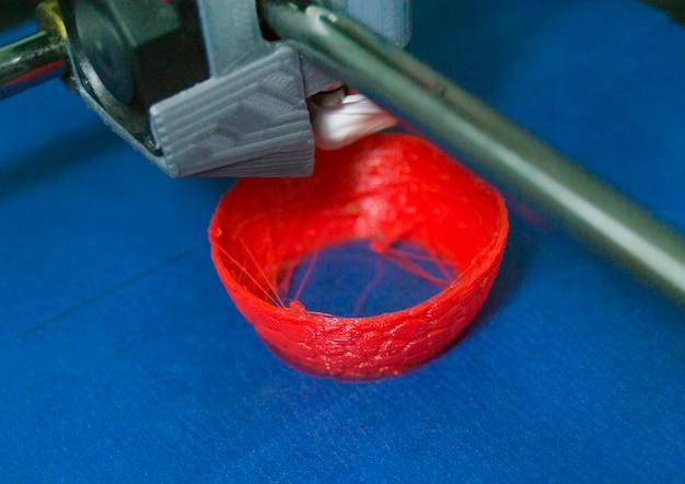 Объекты, напечатанные на 3d-принтере. автоматический трехмерный 3d-принтер выполняет моделирование пластика в лаборатории. прогрессивные современные аддитивные технологии