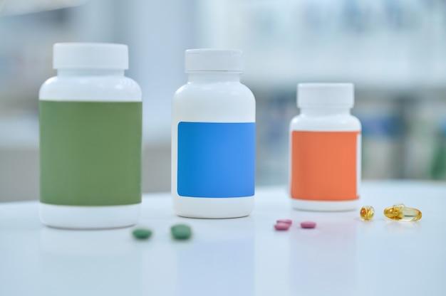 Продолговатые и круглые таблетки разбросаны по столу.