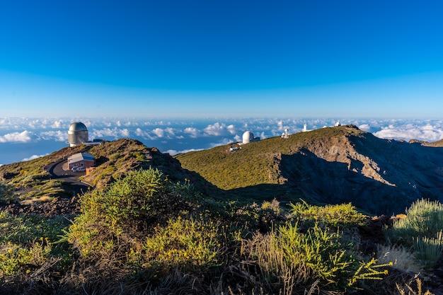 Обсерватории роке-де-лос-мучачос в кальдера-де-табуриенте с морем орехов под одним летним днем, ла-пальма, канарские острова. испания