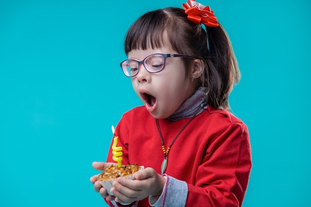 Observing cupcake. curious pretty girl blowing out yellow candle stacked in little cupcake