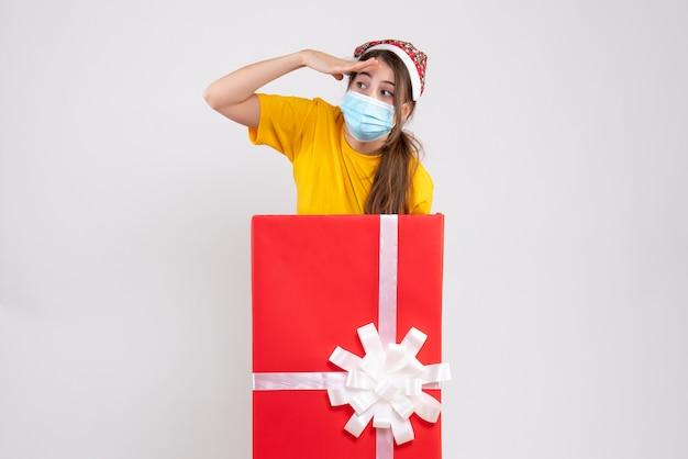 Наблюдая за девушкой в новогодней шапке, стоящей за большим рождественским подарком на белом