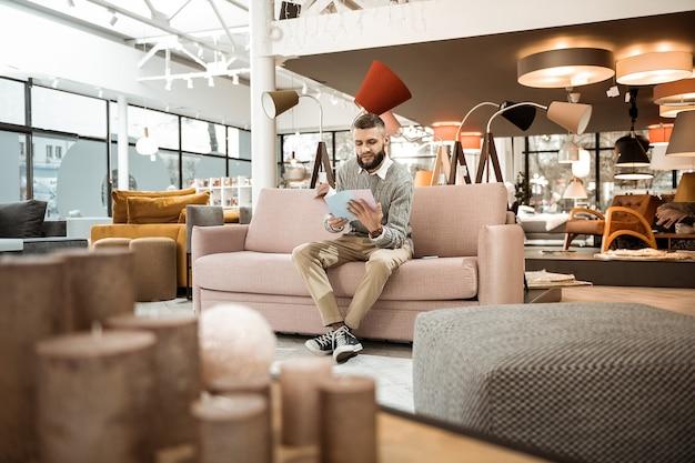 Наблюдательный журнал. любопытный бородатый мужчина рассматривает каталог с вариантами мебели, сидя посреди мебельного магазина