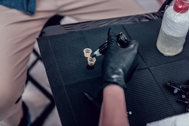 スケッチを観察します。ゴム手袋を着用し、機械用の特別なカップに色付きのインクを混ぜるプロのタトゥーマスター