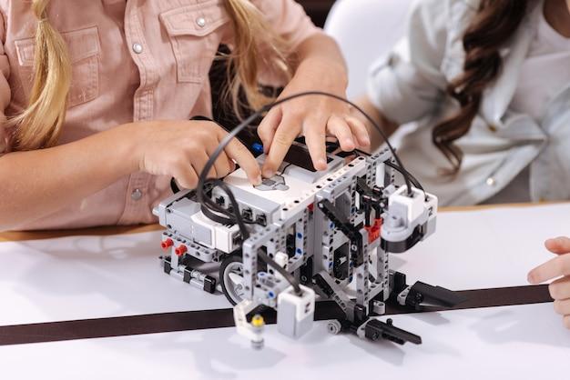 Наблюдая за техническим прогрессом. изобретательные умелые умные дети сидят в школе и наслаждаются уроками техники, конструируя робота