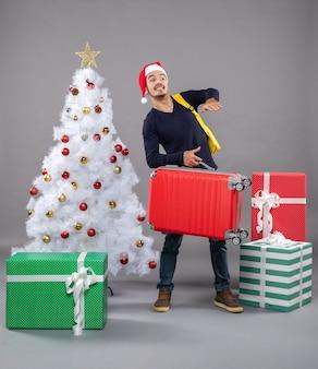 Osservando il giovane con la valigia rossa su grigio isolato