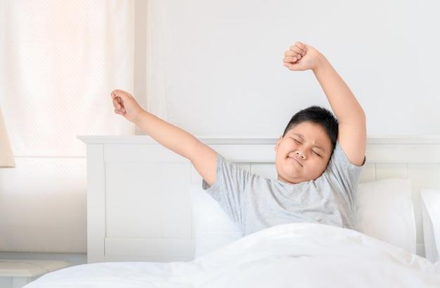 뚱뚱한 소년이 침대에 앉아 스트레칭을 강요합니다.