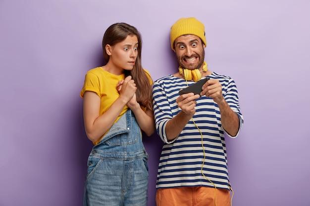 取りつかれたカップルはスマートフォンでビデオゲームをプレイし、ディスプレイを神経質に見て、勝ちたいと思って、ファッショナブルな服を着て、興奮した表情を心配し、紫色の壁に隔離されました。若者、中毒