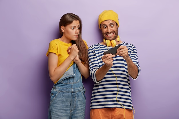 Obsessed couple play video game on smartphone, look nervously at display, eager to win, wear fashionable clothes, have worried excited expressions, isolated over purple wall. youth, addiction
