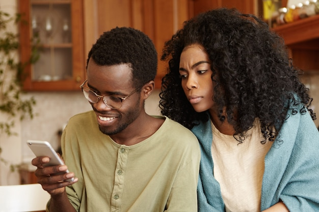 Obsessed possessive young afro-american female looking over her husband's shoulder, trying to read messages on his mobile phone. people, relationships, privacy, infidelity and modern technologies