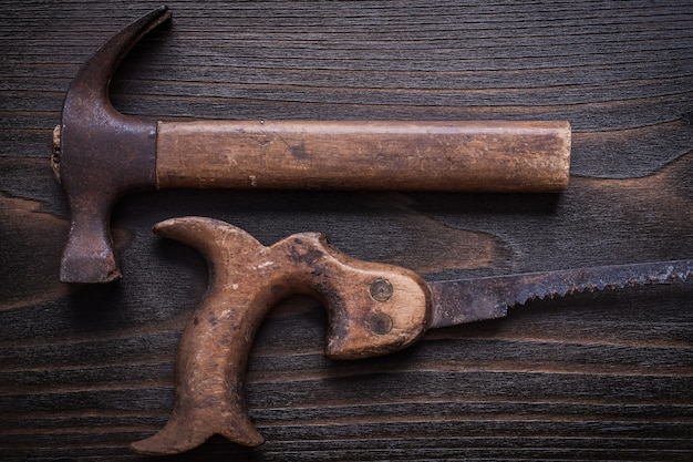 Obsolete rough handsaw and claw hammer on vintage wooden board