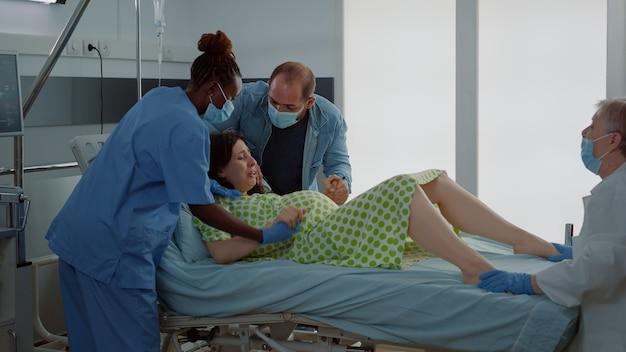 病棟での出産を支援する産科医とアフリカ系アメリカ人看護師。痛みを伴う子宮収縮で出産中の妊婦が赤ちゃんを押しています。サポートのために座っている若い夫
