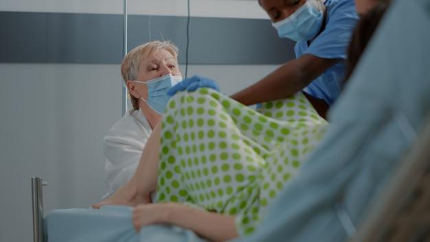 Medico ostetrico che consegna bambino per donna caucasica nel letto del reparto ospedaliero. infermiera afroamericana che aiuta lo specialista con il parto. giovane paziente che partorisce con persone multietniche