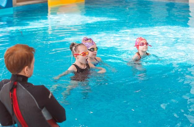Занятие в бассейне детей с тренером по плаванию.