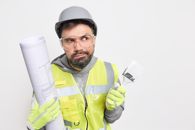 Occupation job career concept. serious working man has pensive expression holds blueprint for constructing future buildig paint brush wears safety helmet glasses and uniform blank space on right
